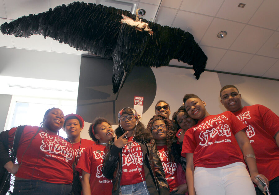 Students in red t-shirts standing below a sculpture of a vulture that has a camera for a head.