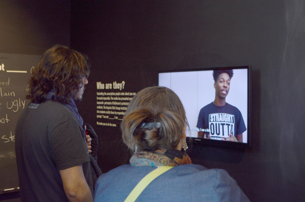 Two people are watching a video of a student speaking in the exhibition.