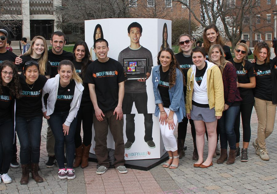 A group of students around a pillar showing images of other students.