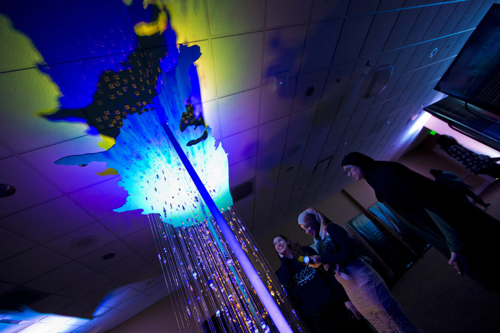 Students shine a blacklight on a beaded sculpture.