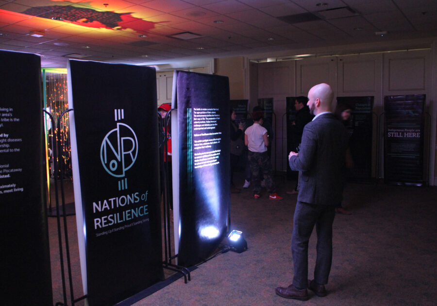A visitor to the exhibit looking at the Nations of Resilience logo