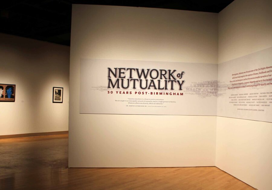 Network of Mutality title card on the entry wall. Art can be see in the background.