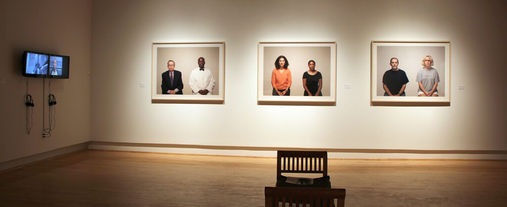 A view of photos of pairs of people. Two chairs are placed for viewing.